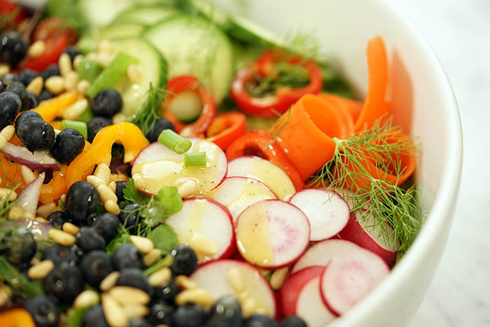 A fresh garden salad recipe with vegetables, blueberries and pine nuts.