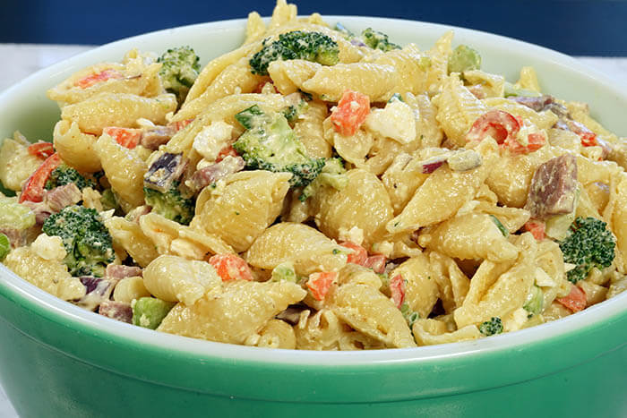 Green bowl filled with Pasta Salad with Cheese, Ham and vegetables.