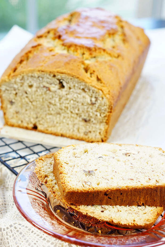 Slices of banana nut bread with the golden delicious loaf nearby, ready to slice off another piece to enjoy!