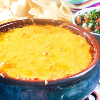 Refried Bean Dip topped with melted cheese in a blue ceramic bowl