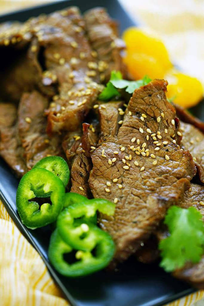 A black platter filled with slices of beef garnished with slices of jalapeños and mandarins.