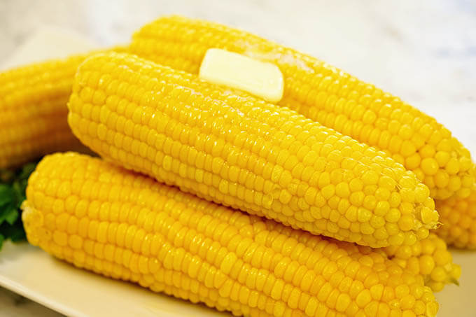 A white platter filled with corn cooked in a pressure cooker.