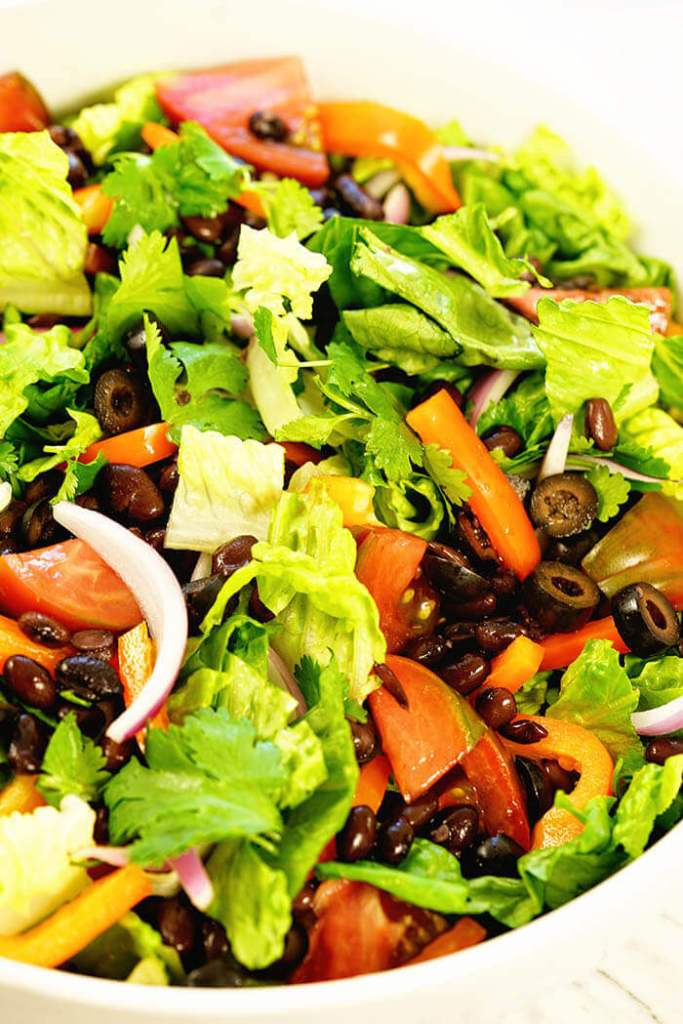 Big green salad in a white bowl with plenty of crunchy fresh ingredients.