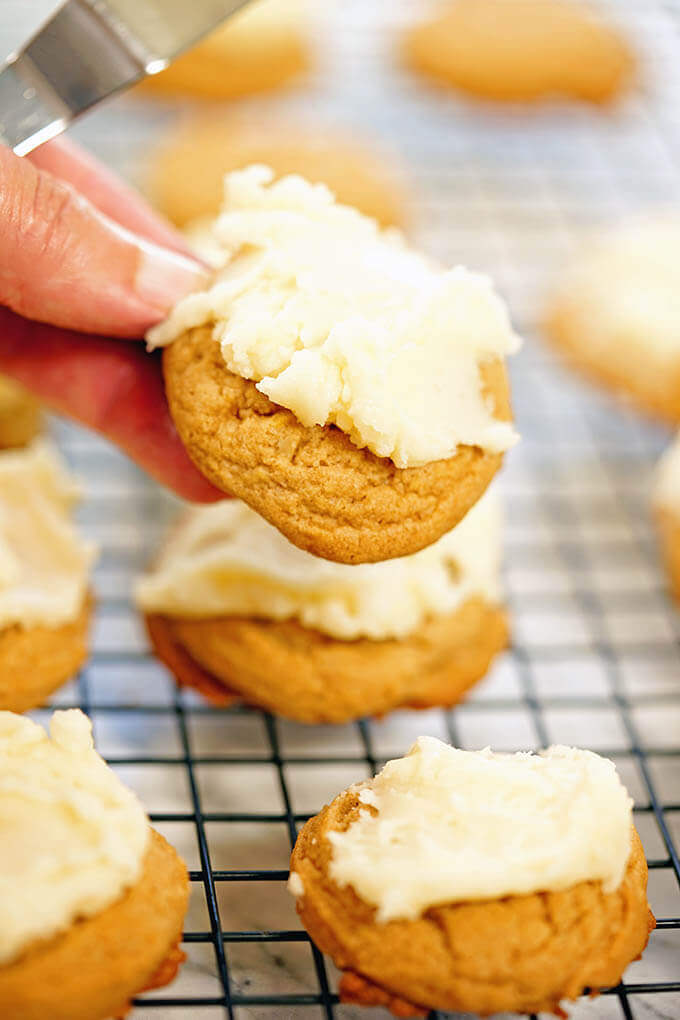 Butterscotch cookie recipes - a panful of cookies with one being held up to show.