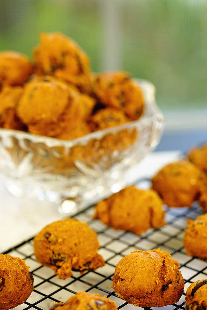 The Best Pumpkin Cookies on a cooling rack with a glass bowl filled with cookies in the background.
