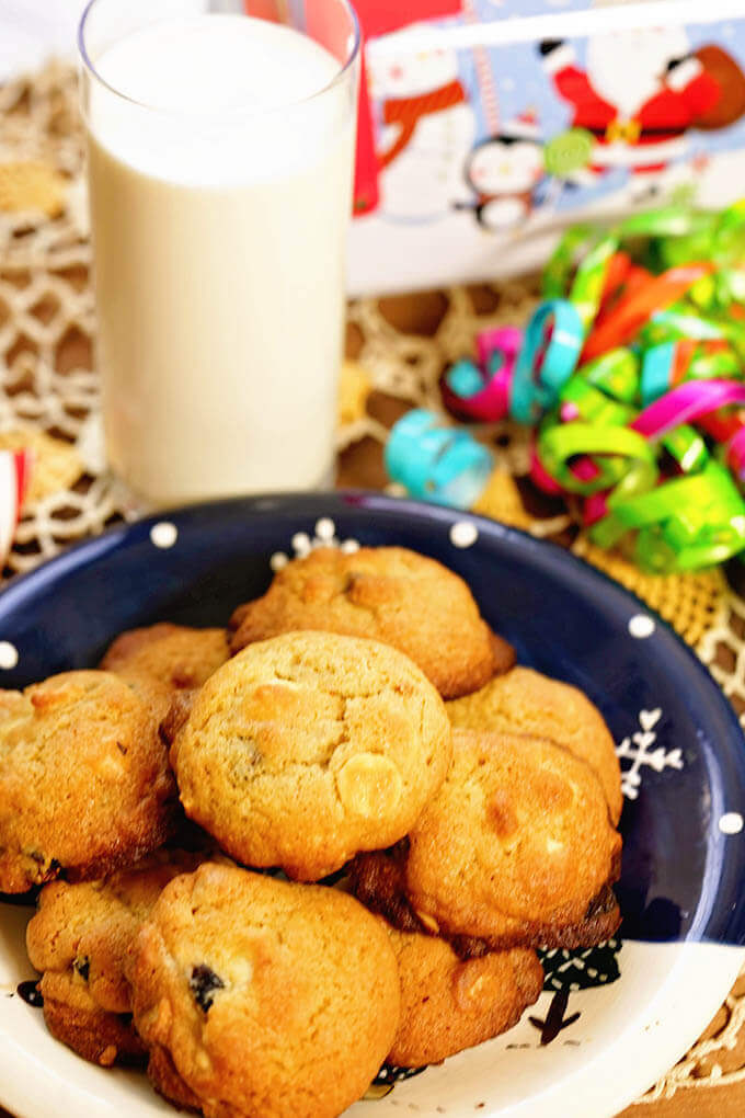 A blue plate filled with White Choc Macadamia Nut Cookies and a glass of milk