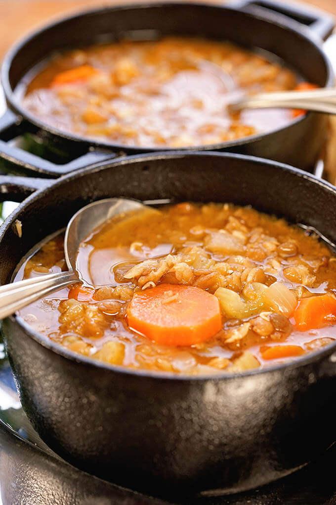 Instant Pot Lentil Soup in black bowls with spoon.