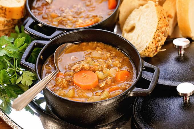 Instant Pot Lentil Soup Recipe in black bowl with spoon.