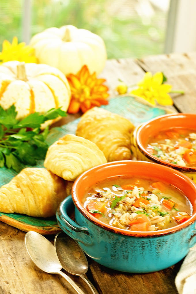 Two bowl of Wild Rice Chicken Soup Recipe service with croissants.