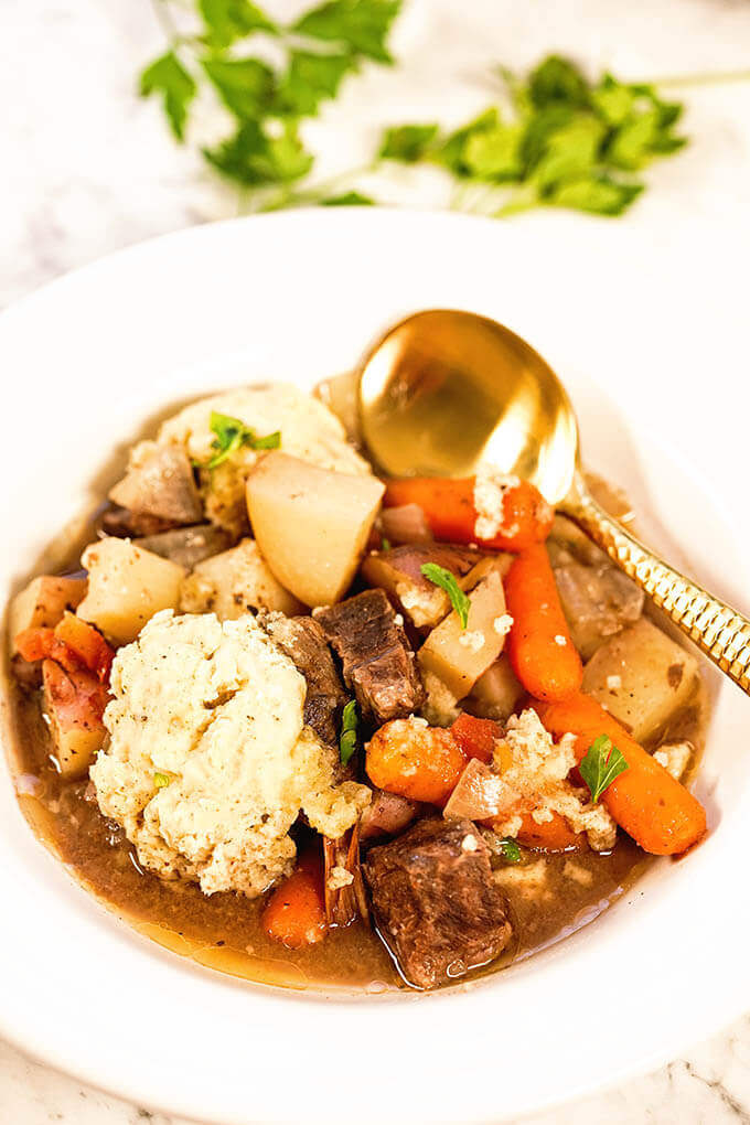 Beef stew with dumplings in a white bowl with spoon.
