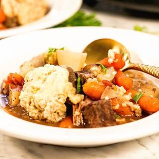 Slow Cooker Beef Stew in a white bowl with spoon on white marble countertop.