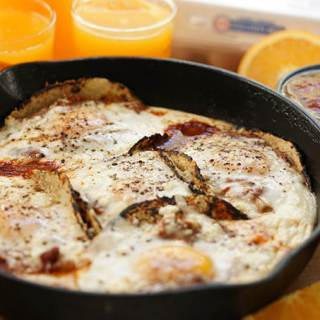 Easy Huevos Rancheros Recipe served with orange juice and a bowl of salsa.