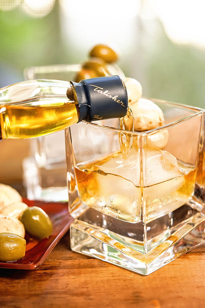 Whiskey pouring into a cocktail glass with an ice cube.