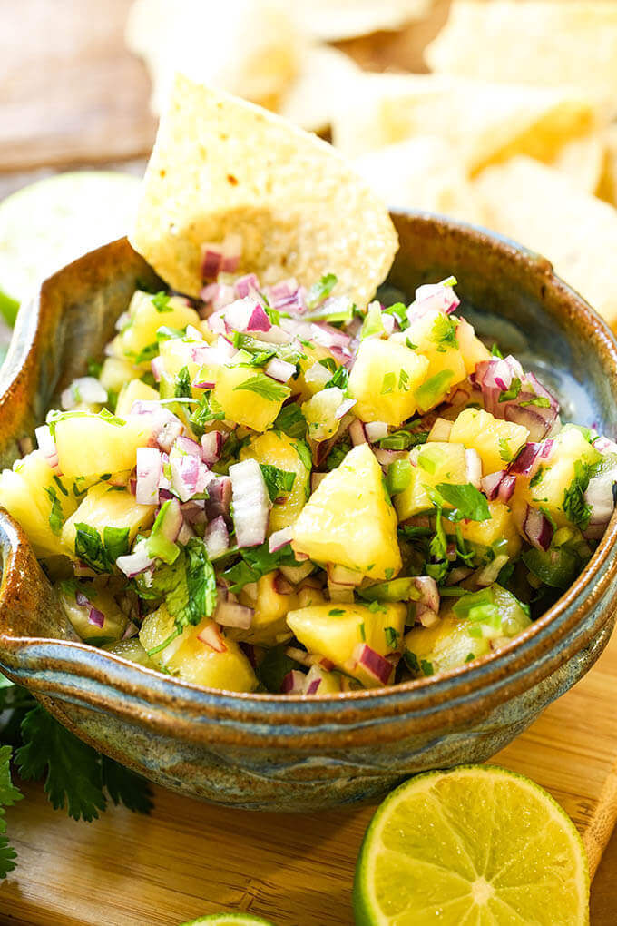 Pineapple Salsa in blue bowl with chips and sliced lime