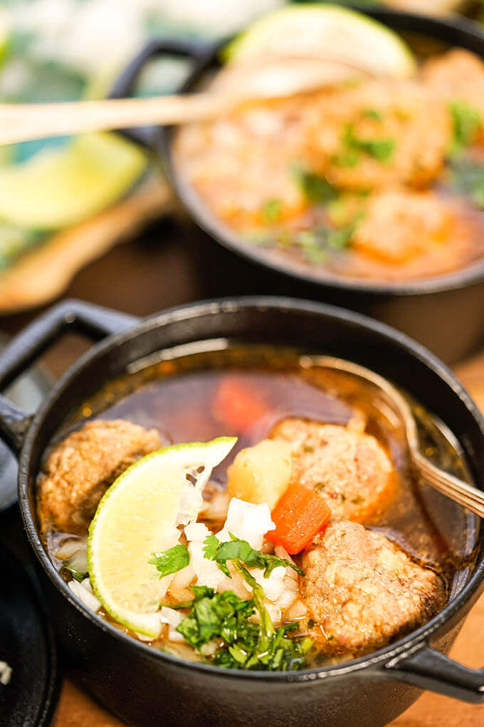 Mexican Meatball soup in black bowl with spoon