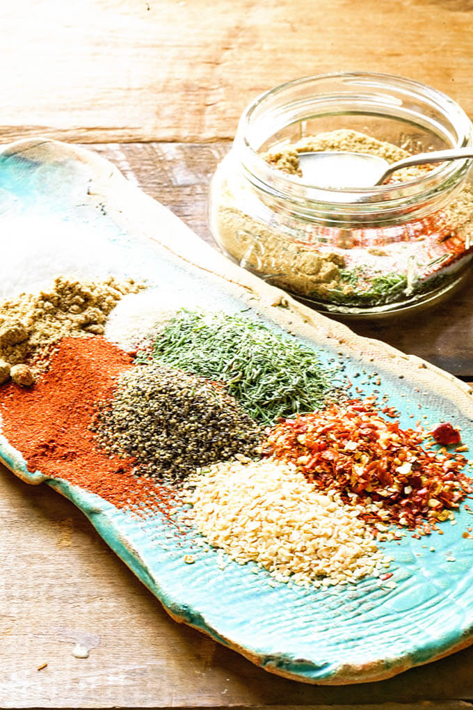 Ingredients for Montreal Steak Seasoning on blue plate and in bowl.