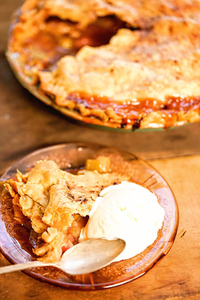 Best Rhubarb Pie on plate with ice cream and spoon