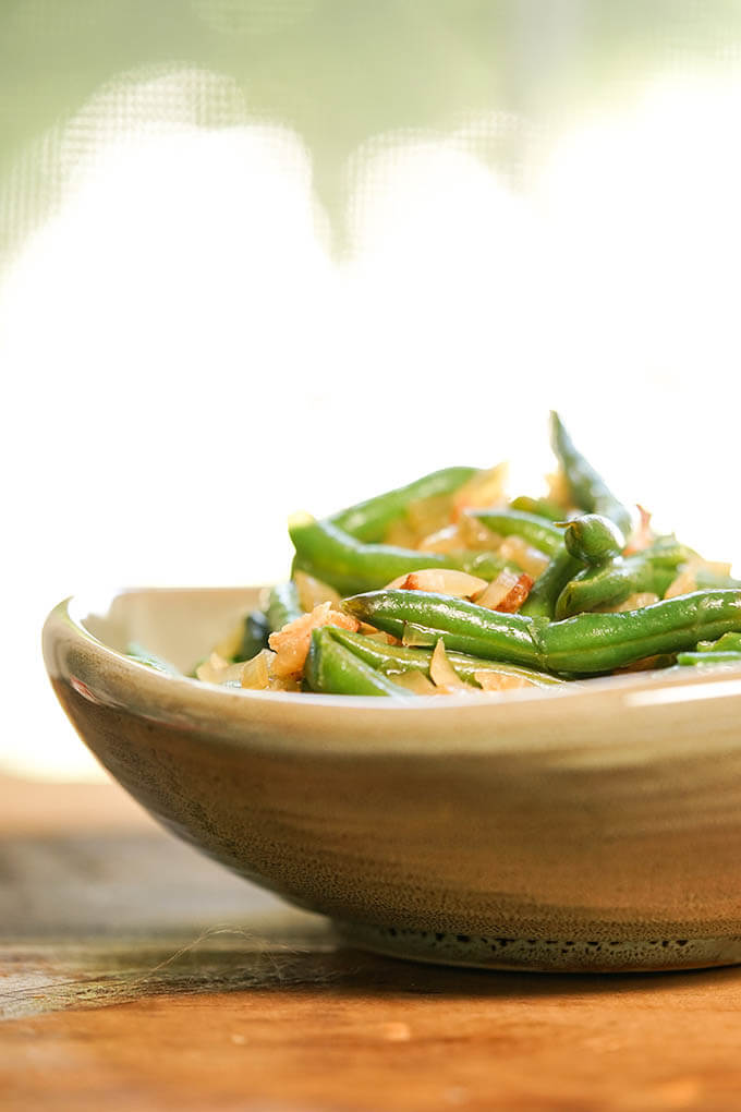 Green beans with bacon and onions in brown bowl
