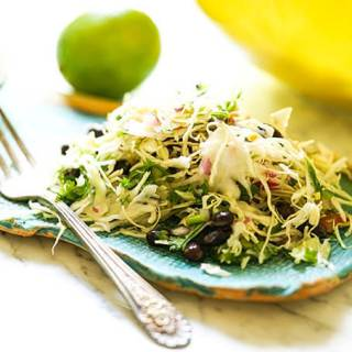 Mexican coleslaw recipe on blue plate with fork.
