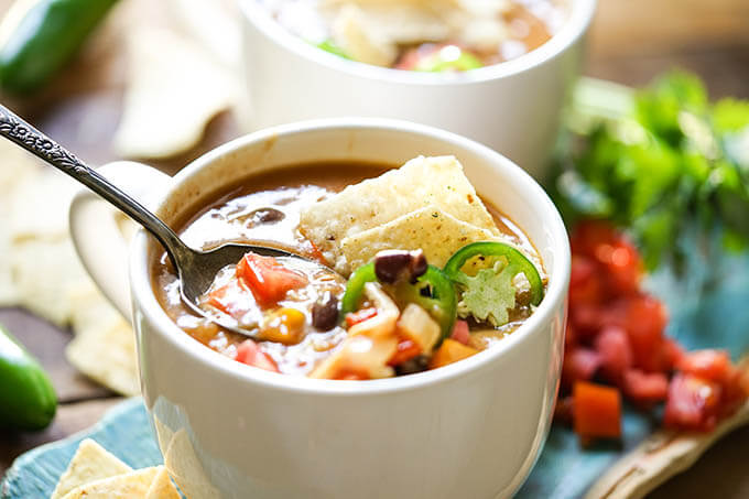 Creamy chicken enchilada soup in white bowl with spoon.