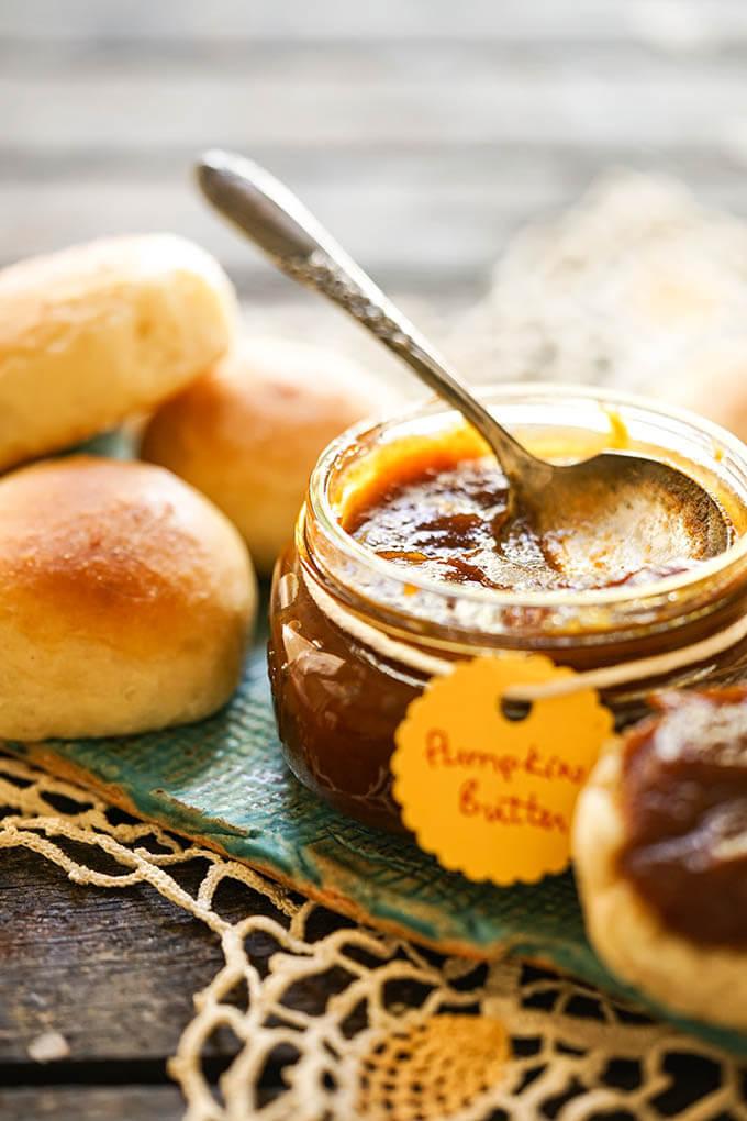 Easy Pumpkin butter Recipe in jar with rolls.