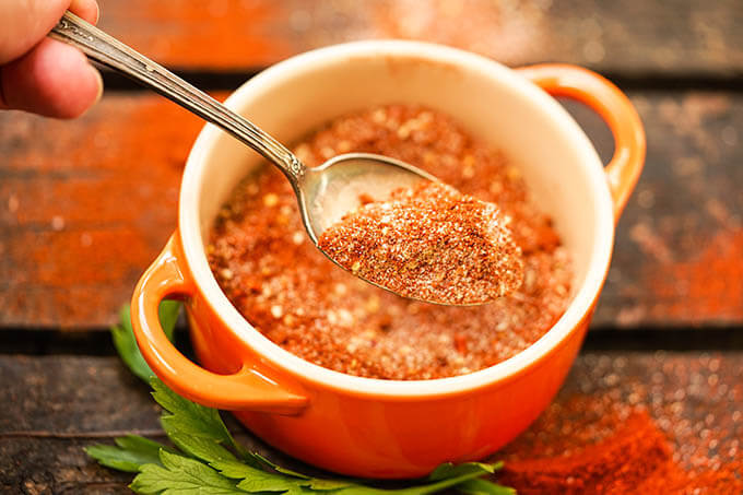 Dry spice mix in orange jar with spoon.