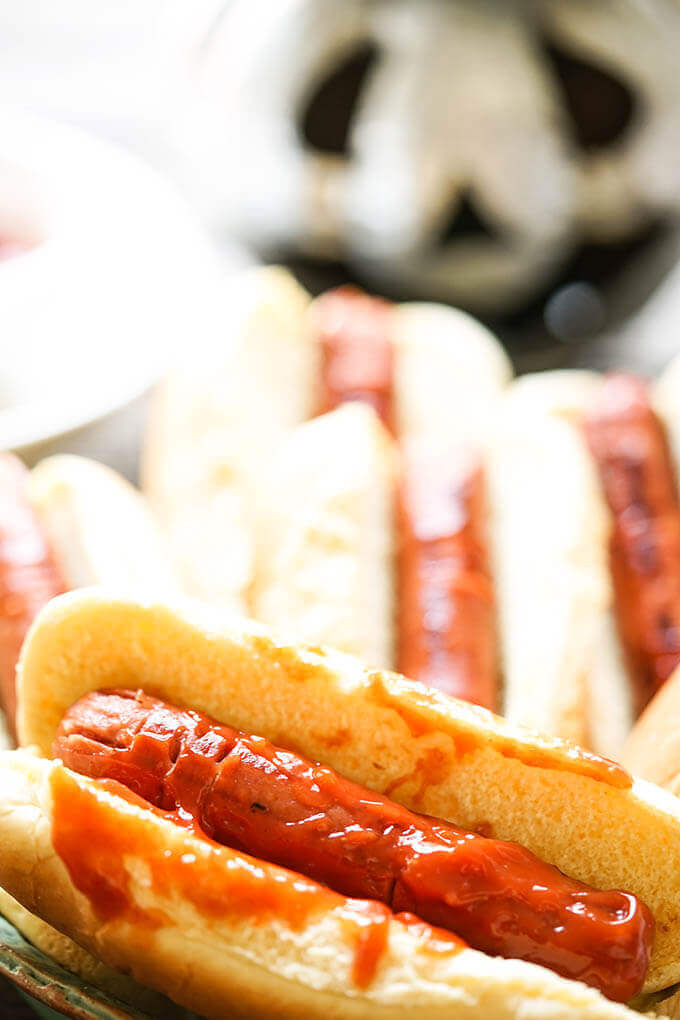 Hotdogs in buns decorated for Halloween