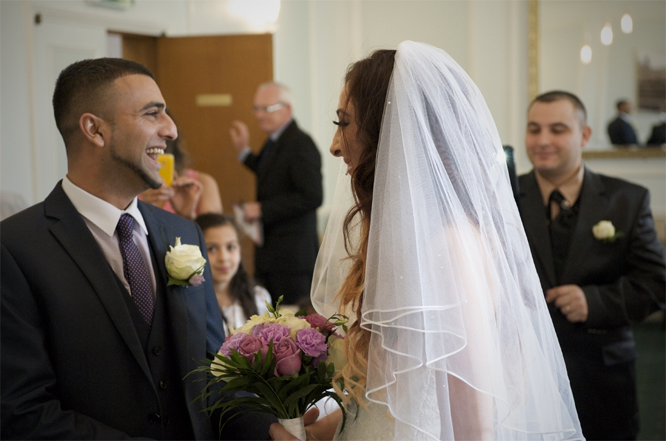 The bride and Groom laugh during the wedding ceremony of Adnan and Jasmina by Cambridge photographer Richard Bowring