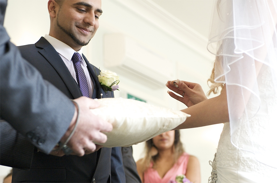 The bride takes the ring from the cussion and prepares to place it on the finger of her husband to be by cambridge photographer Richard Bowring
