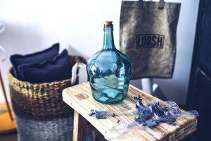 Jarre en verre bleue sur une table en bois clair avec panier en osier et coussins en tissu