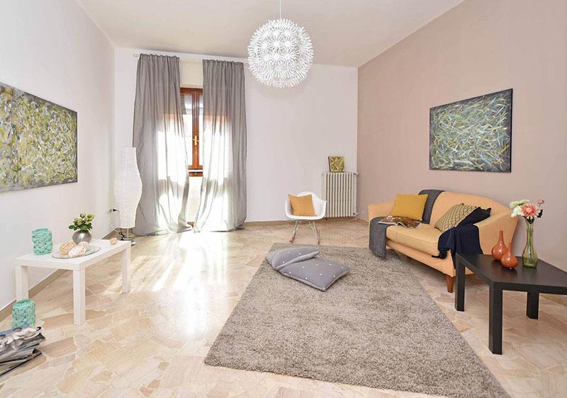 salon couleurs pastel et canapé corail avec voilages beige et objets décoration colorés
