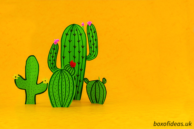 Family of paper cacti crafts placed in front of a dessert looking backdrop #cacti #papercrafts #papercraft #kidscraft #finemotorskills