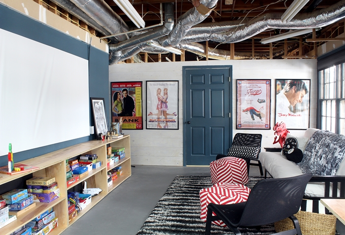 basement movie room with diy plywood shelves and projector screen