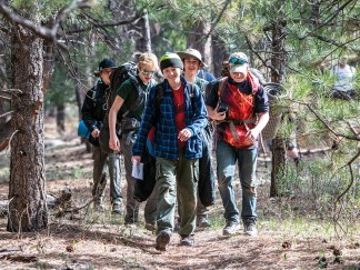 A patrol hikes to a Survivorman Challenge station, where they will be tested on their wilderness survival knowledge.