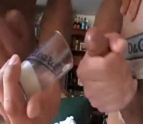 Dois marmanjos enchendo um copinho de porra