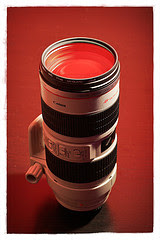 Photograph of a Canon EF 70-200mm f/2.8L IS lens on red background