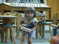 Kid picking up books at Columbia Public Library