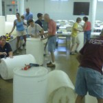 Volunteers make their own rain barrels.