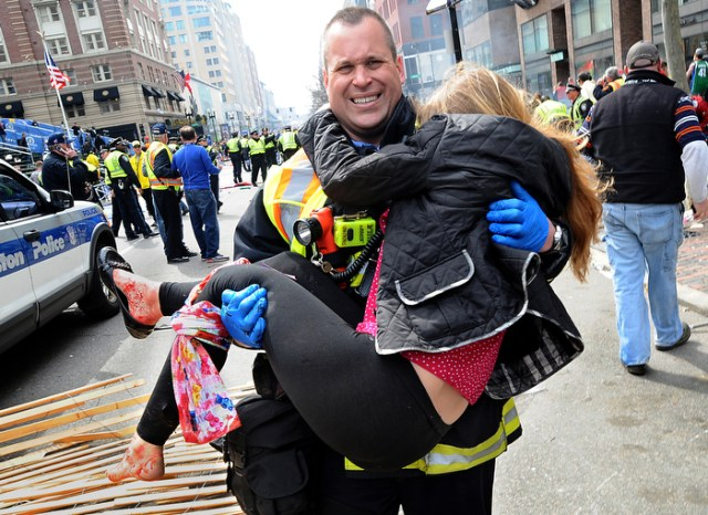 Boston Firefighter James Plourde carries Victoria McGrath, 20,  an injured spectator,  from the scene of the Boston Marathon bombing on Boylston Street on Monday, April 16, 2013.  Plourde was working a fire department detail near the finish and rushed to the scene immediately after the explosions.