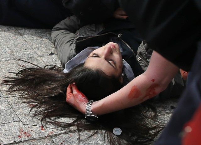 Boston-4/15/13- A man comforts a woman who was hit by shrapnel from the first terrorist bomb on the sidewalk near he finish line of Boylston Street.