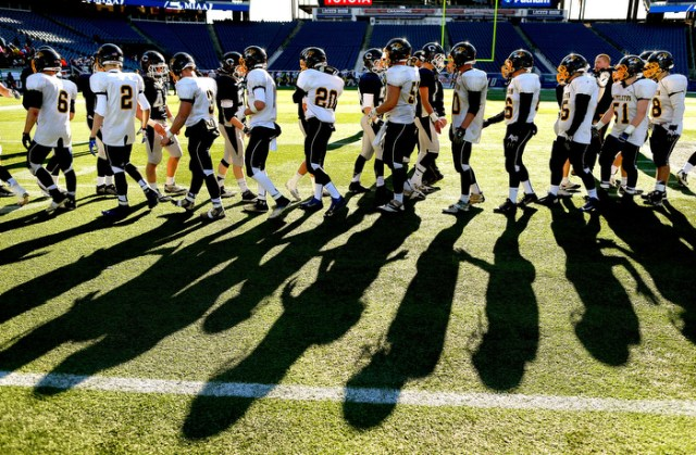 Foxborough12/07/13-  The shadows of Cohasset and Littleton football players shaking hands are cast on the field at the end of the game in which Littleton won the Super Bowl.