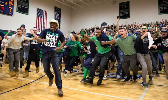 Rasheed Adigun (hat) leads the way as fans swarm the court to celebrate Endicott's 90-70 victory over Wentworth College to clinch the 2014-14 Commonwealth Coast Conference championship. MacDonald Gymnasium, Beverly, MA, 2/28.