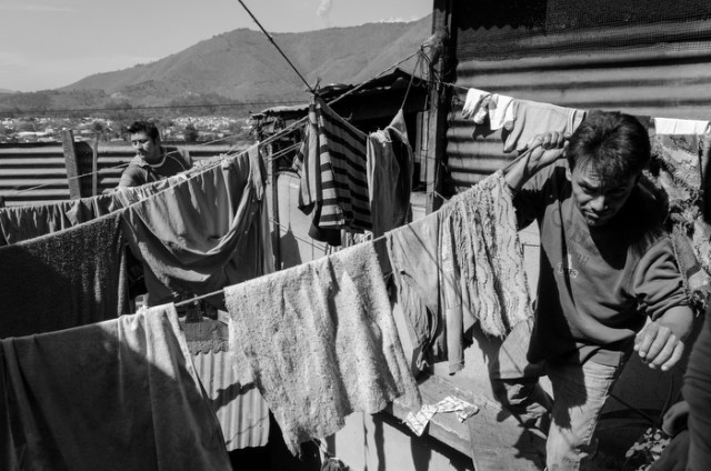 Two members of the program hang and take done laundry from the clothes lines.