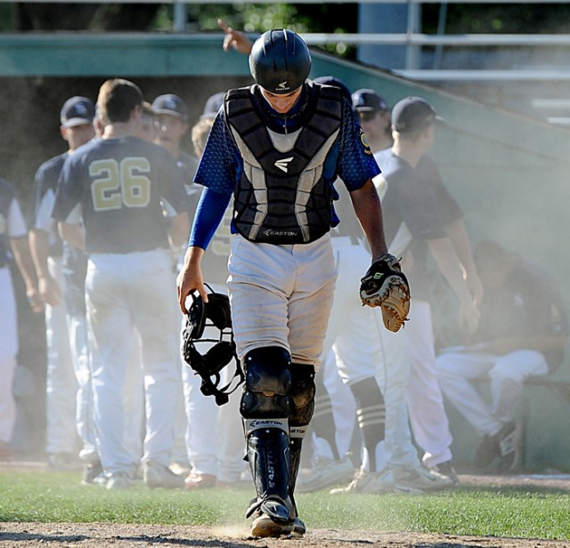 Ashland American Legion Post 77 catcher Sean Jewett walks away as dust rises from scoring Shrewsbury runners  during Post 77's season-ending loss in the American Legion state tournament at Fino Field in Milford.