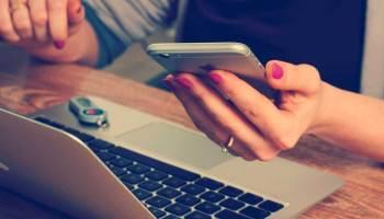 Mulher segurando celular sobre um notebook na mesa de um escritório