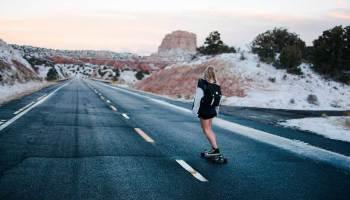 Jovem mulher solitária de skate na estrada deserta