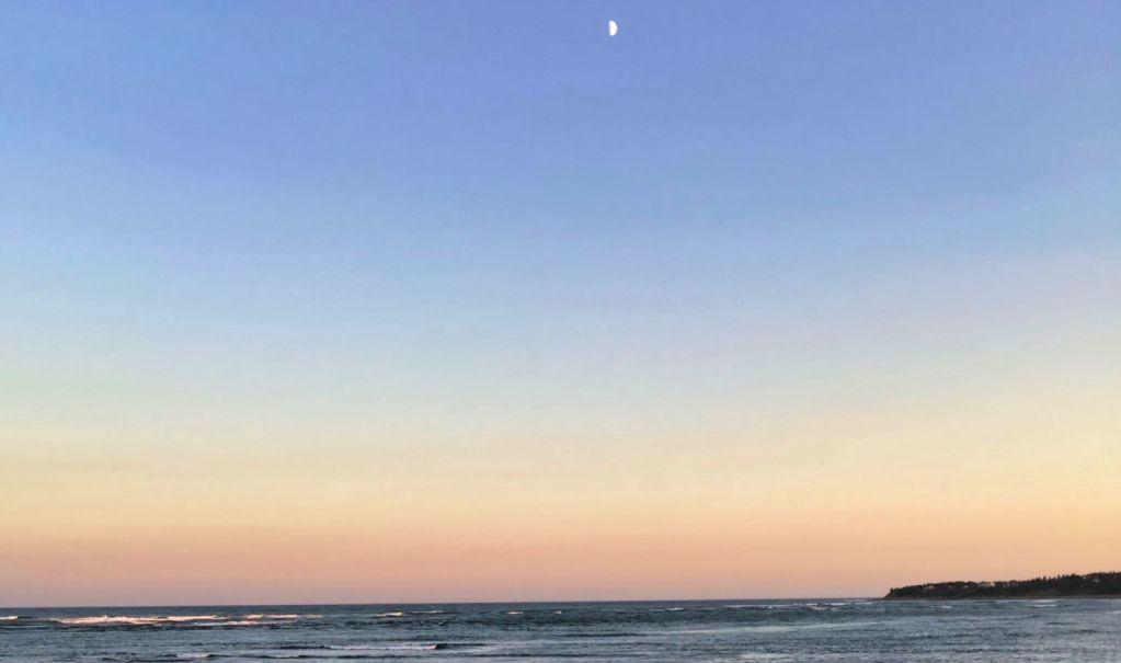 Atlantic coast with the moon visible at dusk
