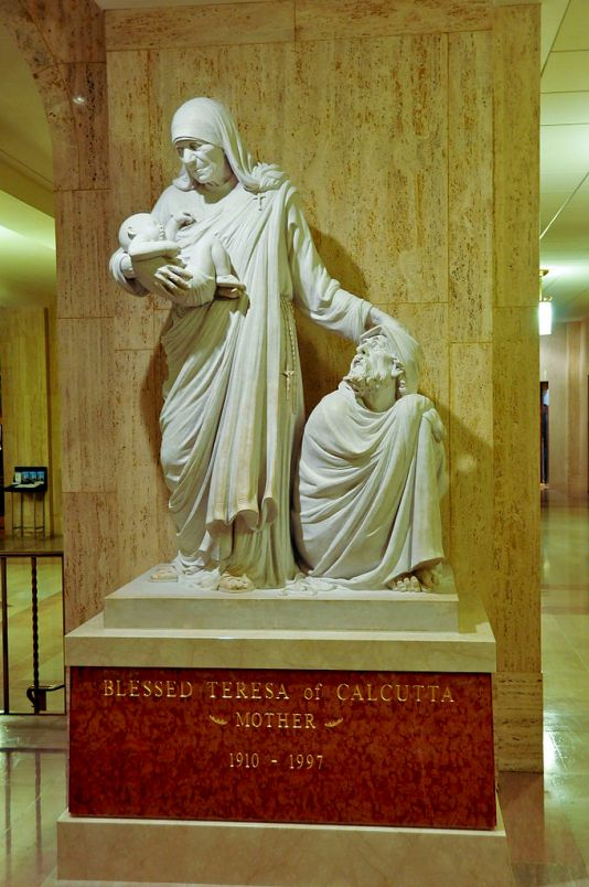A statue of Mother Teresa tending to the young and elderly in Washington D.C.'s Shrine of the Immaculate Conception.