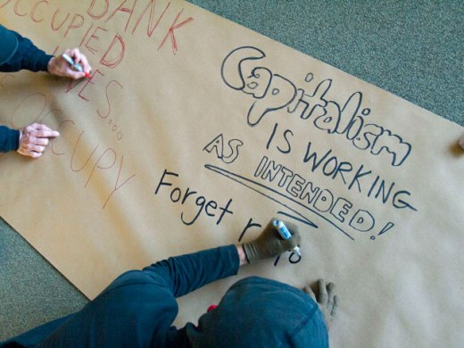 """Photo by Bradley. November 30, 2011. A vacant bank owned by Wells Fargo is occupied in Santa Cruz. An occupier writes """"Capitalism Is Working As Intended!"""" on a banner."""