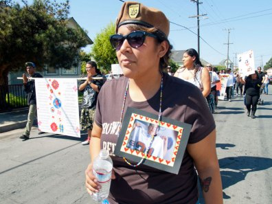 Frances of the Watsonville Brown Berets Wearing a Photo of Jesse Lopez